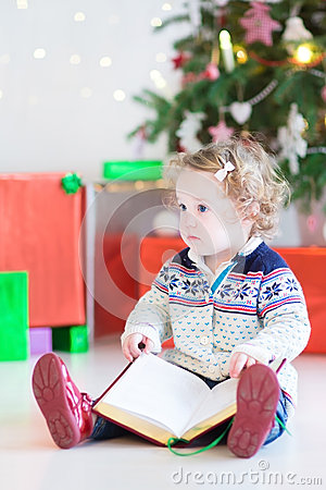 Cute toddler girl reading a book under a Christmas tree