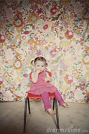 Cute toddler girl sitting on a red chair