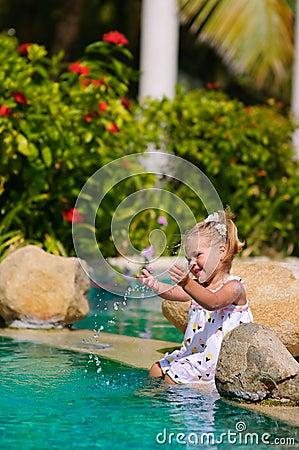 Cute toddler girl splashing in swimming pool