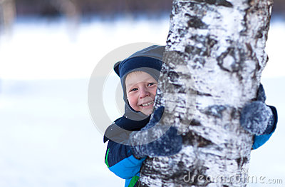 Cute toddler hiding behind a birch tree