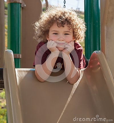 Curly haired boy on slide
