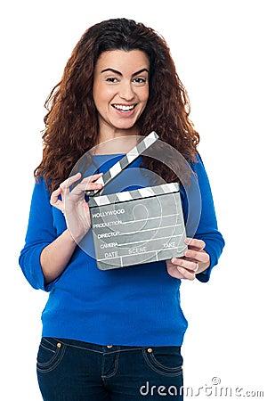 Cute woman in blue attire holding clapperboard