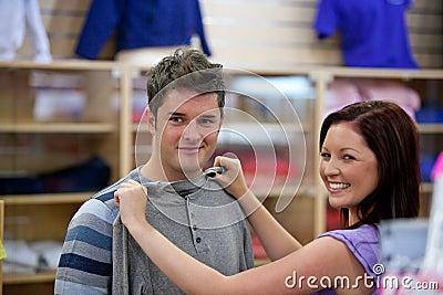 Cute woman choosing clothes for her boyfriend