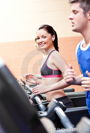 Cute woman with earphones exercising on treadmill