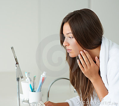 Cute woman looking at her face in the mirror
