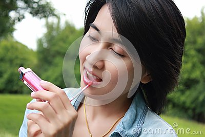 Cute woman looks in mirror also paints lips.