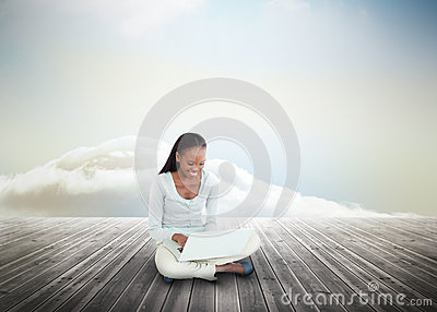 Cute woman using laptop over wooden boards leading out to the horizon