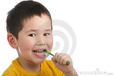 Cute young boy brushing his teeth isolated