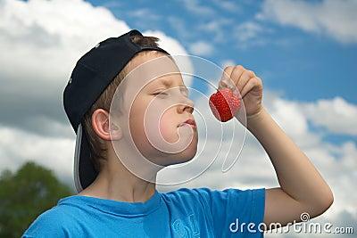 Cute young boy smells or tastes strawberry
