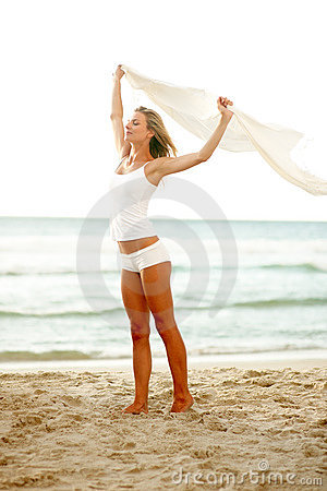 Cute young female with a white shawl at the beach