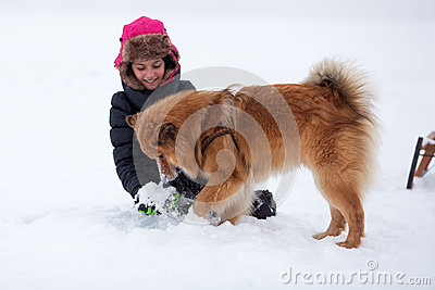 Cute young girl plays with a dog in the snow