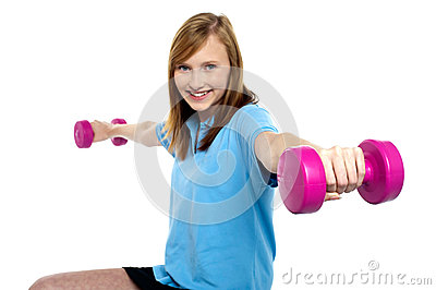 Cute young girl stretching dumbbells sideways