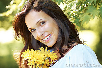 Cute young girl with yellow flowers smiling