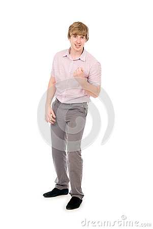 Cute young guy clenching his fist in triumph, isolated over whit