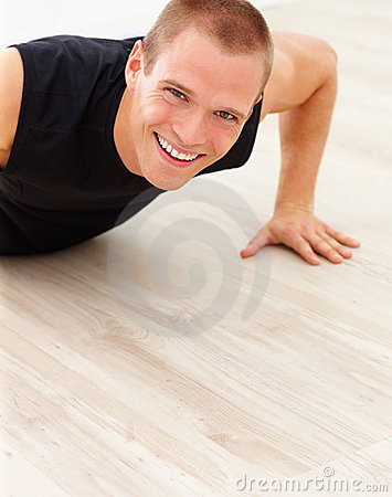 Cute young guy smiling while doing a pushup
