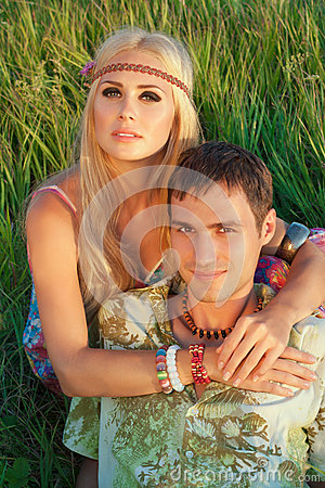 Cute young man and fine woman sit on meadow.