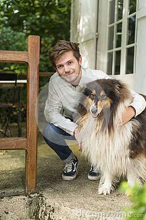 Free Cute Young Man Kneeling With Hairy Collie Dog Outdoors Royalty Free Stock Photos - 77666718