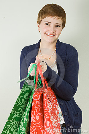 Cute young redhead woman holding shopping bags