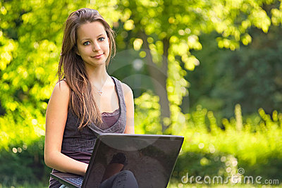 Cute young teen using latop outdoors.