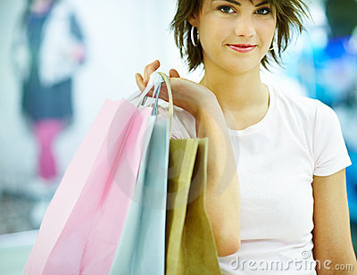 Cute young woman holding shopping bags
