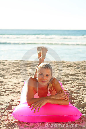 Cute young woman on a pink water float