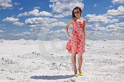 Cute young woman in red dress on the snow