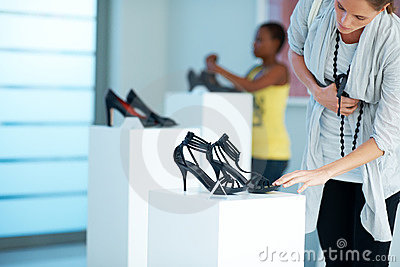 Cute young woman selecting shoes at a store