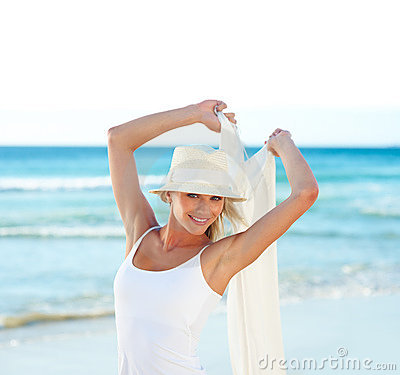 Cute young woman with a shawl at the beach