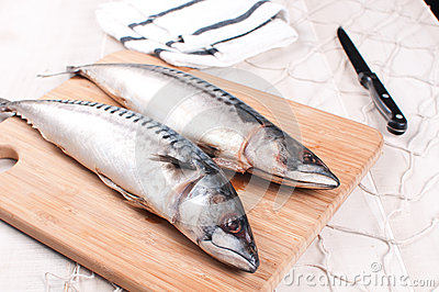 Cutting board with raw mackerel and knife