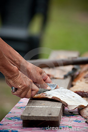 Cutting fish on wooden plank