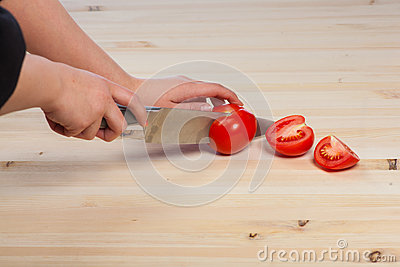 Cutting tomatoes for dishes on the table. Vegetables during the cooking process dishes. Vegetables for healthy eating