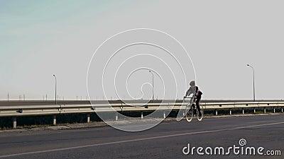 cycling Een mens op een fiets beweegt zich van rechts naar links langs de rand van de weg Sportenlevensstijl Gezonde manier stock video