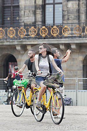 Cycling tourists on Amsterdam Dam Square Editorial Stock Photo