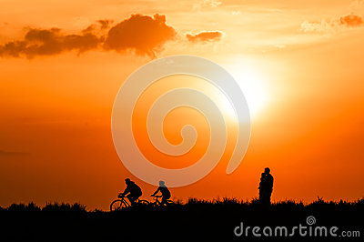 Cyclists and walkers at sunset