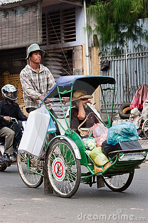 Cyclo driver and his passenger/customer Editorial Image