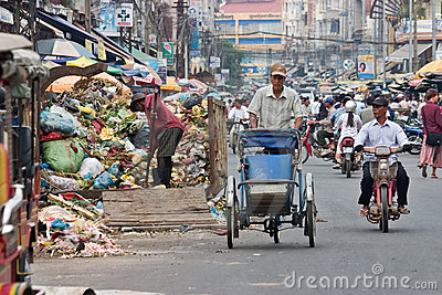Cyclo driver peddling past garbage Editorial Stock Image