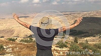 Człowiek stojący na szczycie góry i podnosi rękę, szczytowa przyjemność, łuk, sukces zbiory wideo