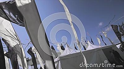 Czarny i biały flaga z taśmami kiwają na wiatrze w letnim dniu Błękita Jasny niebo festiwale namioty biały zdjęcie wideo