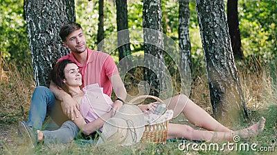 Czas pikniki Szczęśliwa młoda para relaksująca się w parku Facet przytula swoją dziewczynę i wskazuje rękę. Szczęśliwa przyszłość zdjęcie wideo