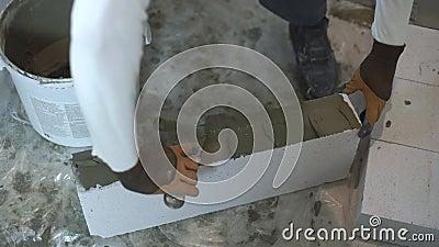 Czasu upływ pracownika budowlanego kładzenia moździerz na wietrzącym betonowym bloku zbiory