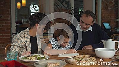 Déjeuner en famille, les parents aident leur fille à écrire quelque chose banque de vidéos
