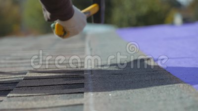 Détenir un toit souple Travail en hauteur Fixation d'une feuille de matériau au moyen de clous et d'un marteau Travail cool des clips vidéos