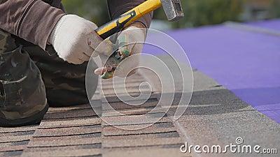 Détenir un toit souple Travail en hauteur Fixation d'une feuille de matériau au moyen de clous et d'un marteau clips vidéos