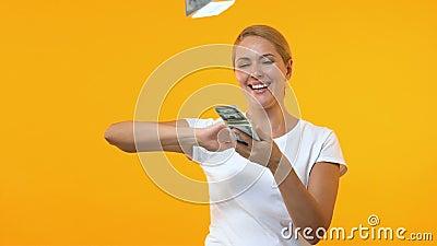 Dólares de jogo da mulher extremamente feliz contra o fundo alaranjado, vencedor de loteria vídeos de arquivo