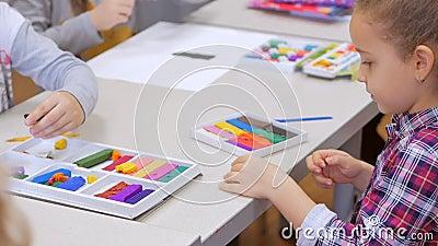 Dłonie dzieci, zbliżenie dzieci, rzeźba z plastyny przy stole, krąg rozwojowy dzieci do rysowania zbiory