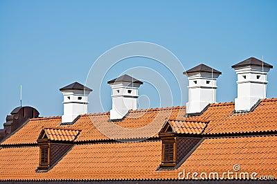Dach der roten Fliese und weiße Kamine