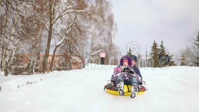 Dad Pushes Her Daughter On A Rubber Inflatable Snow Tube
