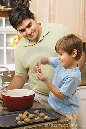 Dad and son making cookies.