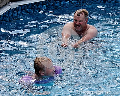 Dad and Son Playing in the Swimming Pool
