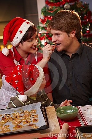 Dad tasting christmas cake with wife and kid